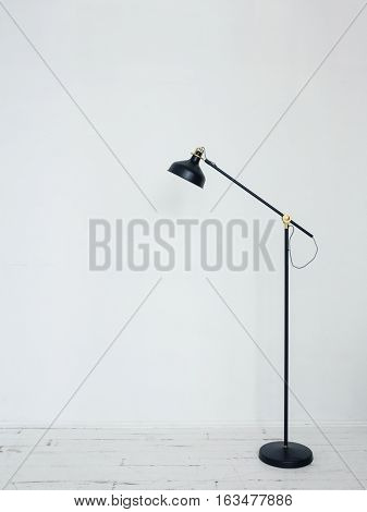 Black floor lamp in interior Modern floor lamp standing in white room with wooden floor