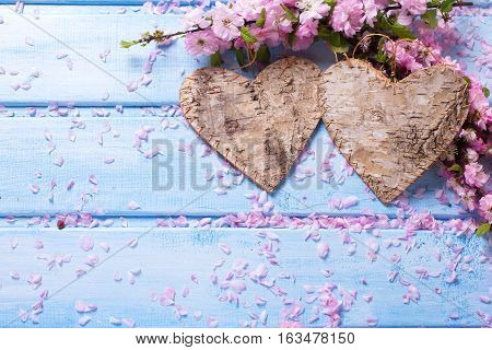 Two decorative hearts and pink sakura flowers on blue wooden background. Selective focus. Place for text.