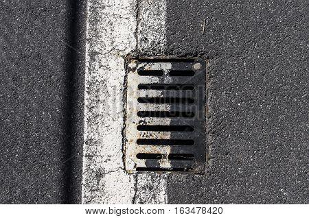 Manhole / Sewer grid on the asphalt. White stripe on the asphalt