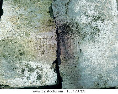 Grietas en cemento con manchas de pintura y humedad