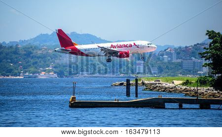 RIO DE JANEIRO, BRAZIL - DECEMBER 28, 2016: Avianca Airlines aircraft flying over Guanabara Bay and landing at the Santos Dumont Airport, Centro district, Rio de Janeiro, Brazil