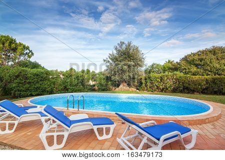 Pool in garden with sun beds for relaxation. With pure water.