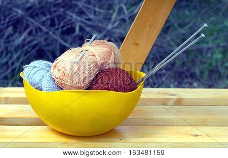 Color skeins of wool yarn, knitting needles and crochet hook in a big yellow bowl on wooden shelf outdoor. Photo closeup