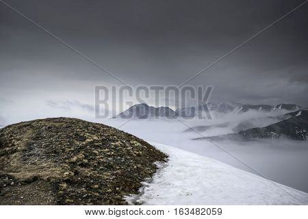 Dark mountain landscape. Snowy mountains in the deep fog. No Man's land