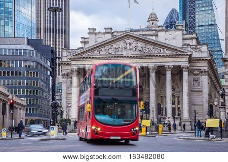 London England - The Royal Exchange building with moving traditional red double decker bus