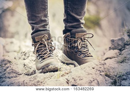 Girls hiking boots. Mountain landscape. Dirty earth and stones