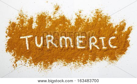 Turmeric powder sprinkled on a natural background. The word turmeric is spelled out across the powdered surface.