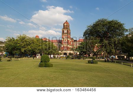 YANGON MYANMAR - NOVEMBER 26 2016: The red building of High Court Palace is listed on the Yangon Heritage List. It is located near the City Hall the Independence Monument and the Maha Bandula Park