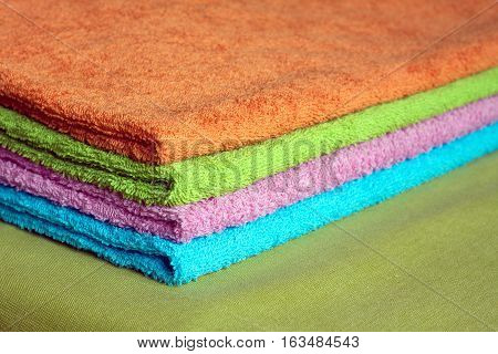 Four clean soft double bath towels set of different colors stacked, lying on the green cloth. Side view closeup
