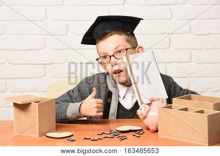 young cute pupil boy in grey sweater and glasses sitting at desk with copybook in hand wooden numbers pink piggy pig bank in graduation cap in classroom showing cool on white brick wall background