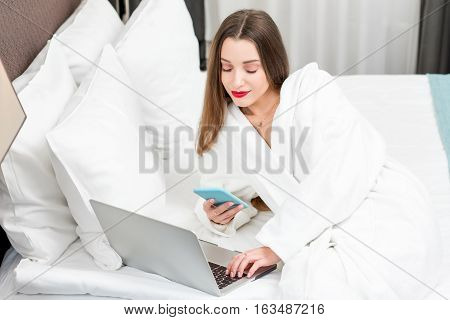 Young woman in bathrobe with laptop and phone on the bed in the hotel room or bedroom