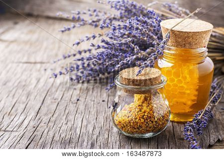 Arrangement of small glass jars with lavender honey, honeycombs and bee pollen with a bunch of dried lavender on dark wooden background. selective Focus