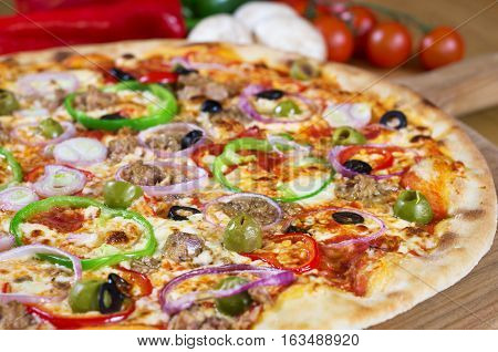 Homemade Tuna Pizza onions, olives, bell pepper on wooden background