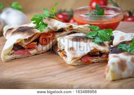 Pizza calzone in the form of cutting with close up on a wooden background
