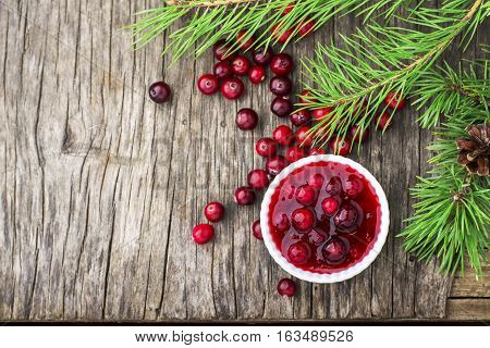 Fresh homemade cranberry sauce in a pan on dark wooden background with scattering of ripe berries. Top view