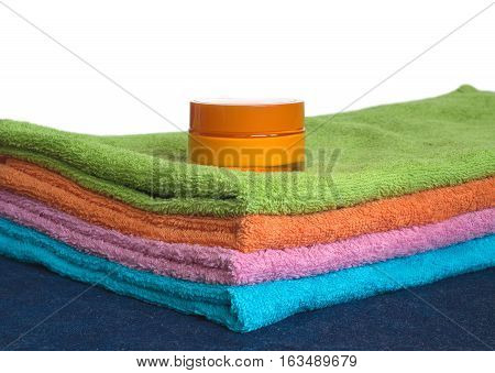 Four clean soft double bath towels set of different colors stacked and jar of cosmetic skin cream on table with denim cloth isolated on white. Side view from corner close-up