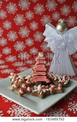 Decorated Christmas honey cookie on red winter background with snow flakes and an angel