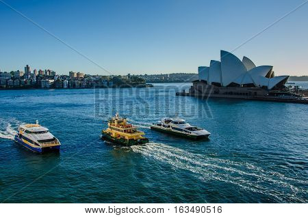 SIDNEY - AUSTRALIA  NOVEMBER 2, 2016: Passenger ferries pass in front of the Sidney Opera House, a multi-venue performing arts center, designed by Danish architect Jorn Utzon.