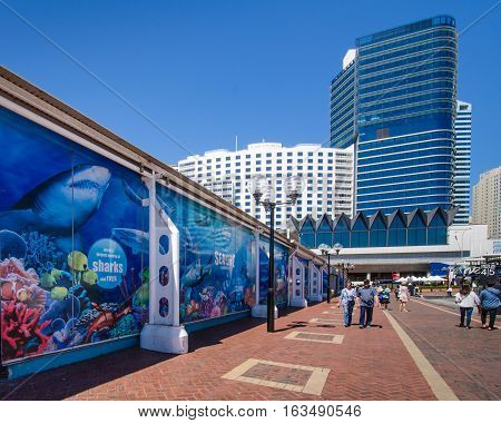 SIDNEY - AUSTRALIA NOVEMBER 2, 2016: Visitors walk along the promenade at Darling Harbour, past the Sea Life Aquarium. The waterfront is one of the city's largest dining, shopping and entertainment districts and a popular destination for visitors.