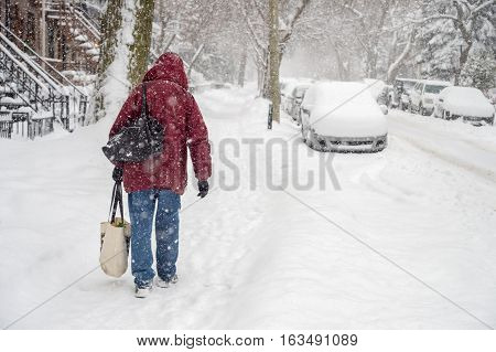 Someone is walking on a snowy sidewalk during snowstorm in Montreal (2016)