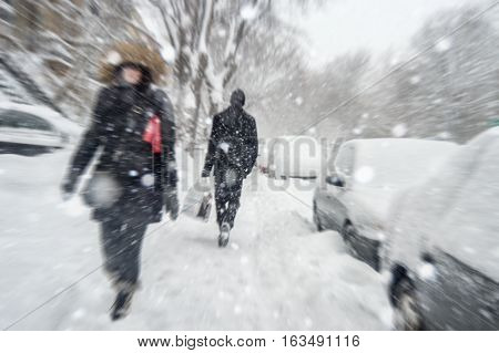 Snowstorm in Montreal. Pedestrians walking on sidewalk with motion blur effect