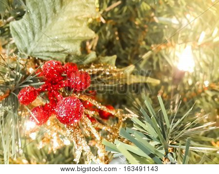 Close up of glistering red artificial berry decorated on a christmas tree with blurred background. Narrow depth of field.