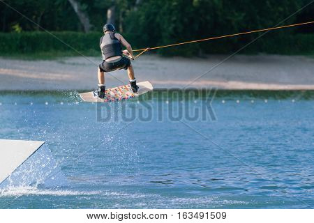 Wakeboarder performing stunt on the platform , toned image