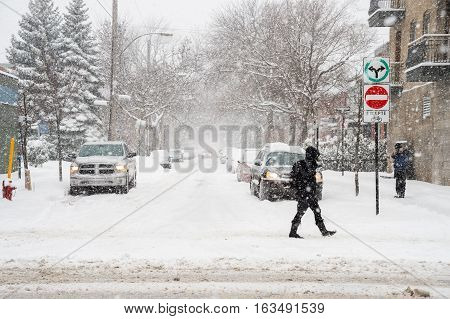 Montreal CA - 29 December 2016: Snowstorm in Montreal. Pedestrians on Mont-Royal Avenue.