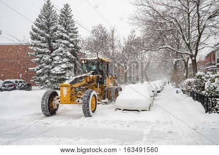 Montreal CA - 5 December 2016: A snowplow in motion on Marquette Street during snow storm.