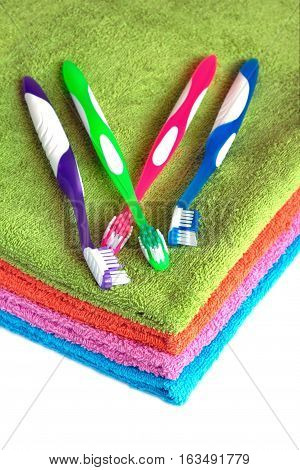 Clean soft double bath towels set of different colors stacked and four toothbrushes isolated on white background. Side view from corner close-up