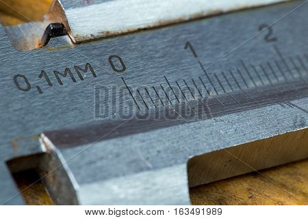 Macro photo, close-up range, high-precision hand-held measuring tools - vernier calipers  brown wooden background