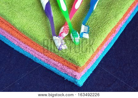 Four new soft double bath towels set of different colors stacked and four toothbrushes isolated on blue denim background. Side view from corner close-up