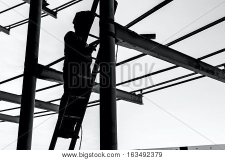 Silhouetted industrial shot of construction worker who is using the wooden ladder to welding metal frame.
