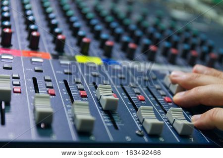 selective focus finger sound tuning of sound mixer close up. stock photo