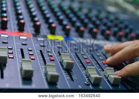 selective focus finger sound tuning of sound mixer close up. studiostock photo