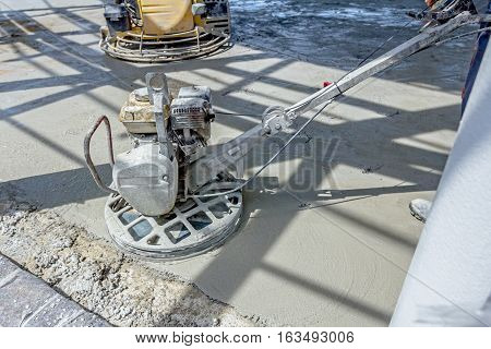 Self leveling power trowel machine sander for smoothing surface to finish concrete slab.