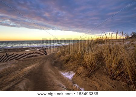 Winter Sunset On The Great Lakes Coast.  Sunset horizon on the windswept shore of the Lake Huron coast in Port Austin, Michigan.