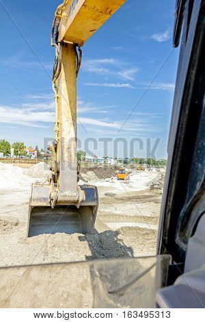 Excavator is digging with his bucket view from inside excavator's cabin.