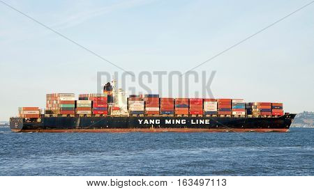 San Francisco CA - December 26 2016: Yang Ming Line cargo ship YM PLUM in the San Francisco Bay en route to the Port of Oakland the fifth busiest port in the U.S.