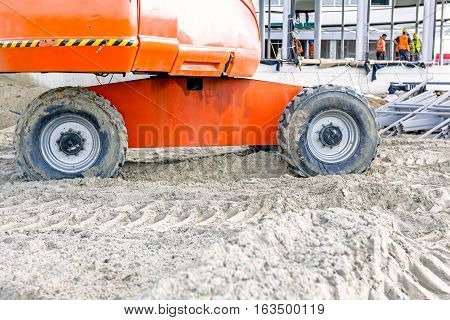 Low angle view on cherry pickers wheels at building site undercarriage.