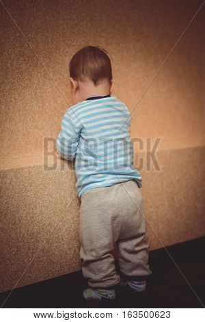 small child standing facing a wall in the apartment
