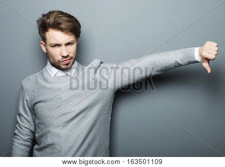 lifestyle, business and people concept: Sad businessman show something over grey background