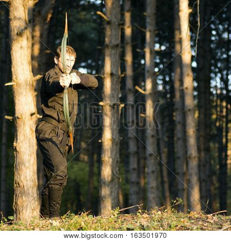 The ninja archer with bow and arrow is in the forest.