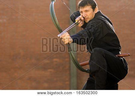 Man in black kimono is practicing archery with traditional hungarian bow and two arrows.