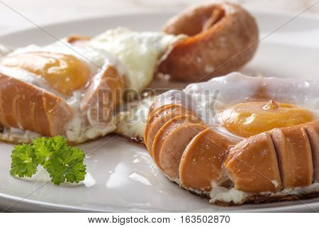 Fried sausages and eggs on white plate