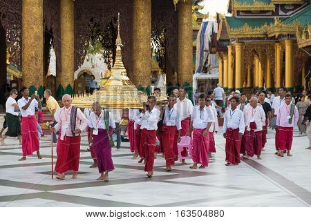 YANGON MYANMAR - NOVEMBER 26 2016: Ordination ceremony at the sunset in the Shwedagon pagoda with monks walking around the pagoda  carrying sacred items