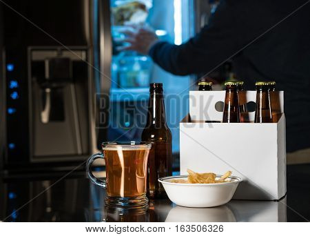 Six pack of brown beer bottles in plain white cardboard carrier with mug of ale on stainless steel kitchen or bar counter. Open fridge or refrigerator out of focus in rear.