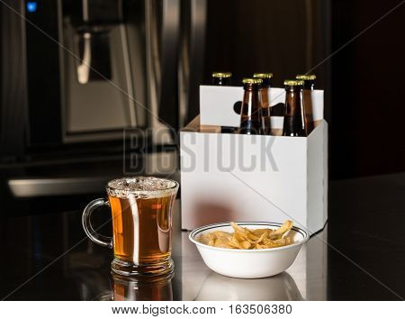 Six pack of brown beer bottles in plain white cardboard carrier on stainless steel kitchen or bar counter with poured ale in tankard