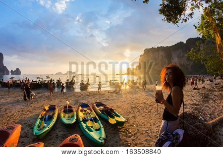 KRABI, THAILAND, 07 JANUARY 2012 : Young woman with a milkshake, kayaks and traditional thai longtail boats at the sunset, Tonsai beach near Railay bay