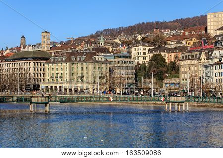 Zurich, Switzerland - 27 December, 2016: view over the Limmat river towards Central square, the Muhlesteg pedestrian bridge in the foreground, people on the embankment of the river. Zurich is the largest city in Switzerland.